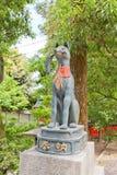 Kitsune fox statue in Fushimi Inari Shrine of Kyoto, Japan. Statue of kitsune with rice sheaf in Fushimi Inari Taisha Shinto Shrine in Kyoto. Kitsune is a fox Stock Photo