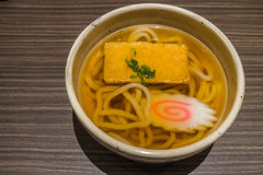 Kitsune Udon Japanese noodles in white bowl on wooden table. Close up Stock Photo