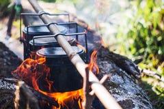 Kitteln kokar på branden som campar i skogen, i att marschera a Arkivbild