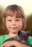 Kitten on arm of the boy outdoors, child huge his love pet Stock Photo