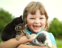 Kitten on arm of the boy outdoors, child huge his love pet Royalty Free Stock Images
