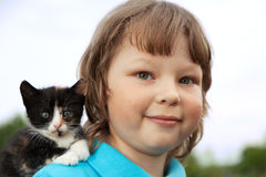 Kitten on arm of the boy outdoors, child huge his love pet Stock Photography