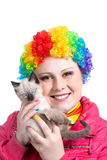 Kitten and clown with rainbow make up. Beautiful woman in rainbow clown wig with freckles and creative rainbow make-up smiling and holding little kitten in her royalty free stock images