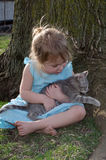 Kitten and girl Lap of love. Littl girl in blue dress holds her new soft kitten on her lap as they sit under a tree in the back yard. a sweet child and her pet Stock Images