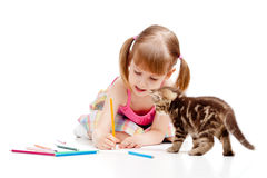 Kitten watching at drawing child girl. Small cat watching at drawing child girl royalty free stock images