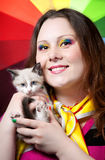 Kitten and Woman with rainbow make up. Beautiful woman with creative rainbow make-up and nails smiling and holding little kitten in her arms at rainbow Stock Photos
