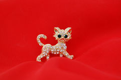 Kitty brooch. With gem stones on red fabric background Stock Images
