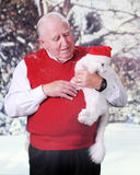 Kitty-Loving Senior. A senion man happily looking at the white cat he's holding.  They are outside in wintertime and the cat wears a Santa hat Stock Photos