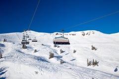 KITZBUEHEL, OOSTENRIJK, 18 Februari, 2016 - Skiërs die bij de skilift van de mening genieten aan mistige Alpen in Oostenrijk en m Royalty-vrije Stock Foto's