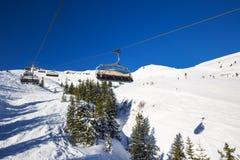 KITZBUEHEL, OOSTENRIJK, 18 Februari, 2016 - Skiërs die bij de skilift van de mening genieten aan mistige Alpen in Oostenrijk en m Stock Foto's