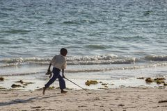 Travel around Tanzania. Little boy running along the coast. stock photo