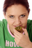 Kiwi. Stock photo of a young woman eating kiwi, diet concept royalty free stock photo