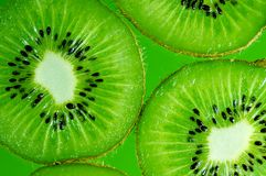 Kiwi. Slices on green background Royalty Free Stock Image