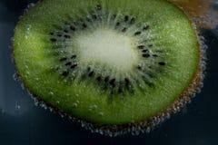 Kiwi affettato in acqua immagini stock libere da diritti