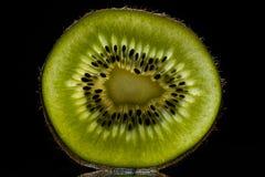 Kiwi affettato con luce posteriore isolata su fondo nero immagine stock