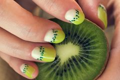 Kiwi art manicure. Kiwi and female hand with green and white moon nail art manicure stock images
