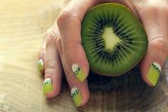 Kiwi art manicure. Kiwi and female hand with green and white moon nail art manicure stock photo