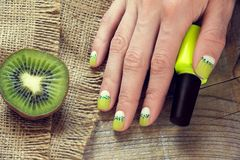 Kiwi art manicure. Kiwi, nail polish and skin care of a beauty female hand with green and white moon nail art manicure on a sackcloth and wooden background stock photo