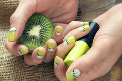 Kiwi art manicure. Kiwi, nail polish and skin care of a beauty female hands with green and white moon nail art manicure on a sackcloth and wooden background royalty free stock photography