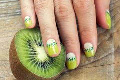 Kiwi art manicure. Kiwi and skin care of a beauty female hand with green and white moon nail art manicure on a wooden background royalty free stock photos