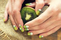 Kiwi art manicure. Kiwi and skin care of a beauty female hands with green and white moon nail art manicure on a sackcloth and wooden background royalty free stock photos