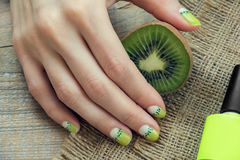 Kiwi art manicure. Kiwi, nail polish and skin care of a beauty female hand with green and white moon nail art manicure on a sackcloth and wooden background stock photos