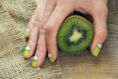 Kiwi art manicure. Kiwi and skin care of a beauty female hand with green and white moon nail art manicure on a sackcloth and wooden background stock photo