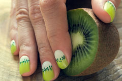 Kiwi art manicure. Kiwi and skin care of a beauty female hand with green and white moon nail art manicure on a wooden background royalty free stock photography
