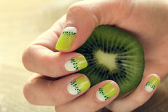 Kiwi art manicure. Kiwi and skin care of a beauty female hands with green and white moon nail art manicure stock images