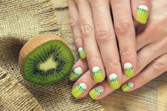 Kiwi art manicure. Kiwi and skin care of a beauty female hands with green and white moon nail art manicure on a sackcloth and wooden background stock photography