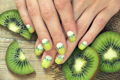 Kiwi art manicure. Kiwi and skin care of a beauty female hands with green and white moon nail art manicure on a sackcloth and wooden background stock images