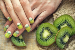 Kiwi art manicure. Kiwi and skin care of a beauty female hands with green and white moon nail art manicure on a sackcloth and wooden background royalty free stock photography