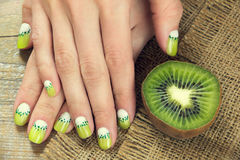 Kiwi art manicure. Kiwi and skin care of a beauty female hands with green and white moon nail art manicure on a sackcloth and wooden background stock photos