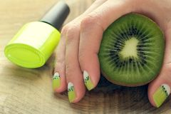 Kiwi art nail manicure. Kiwi, bottle and female hand with green and white moon nail art manicure on a wooden background royalty free stock image