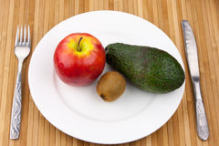 Kiwi, avocado and apple on a plate with cutlery Stock Photo
