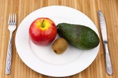 Kiwi, avokado och äpple på en plätera med bestick arkivfoto