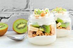 Kiwi, banana, parfait della noce di cocco in barattoli di muratore contro il mattone bianco Fotografia Stock Libera da Diritti