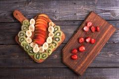 Kiwi, banane et nectarine d'Ut se trouvant sur une planche à découper Photos stock