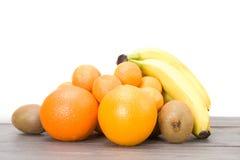 Kiwi, bananen, sinaasappelen en mandarijnen op een houten lijst Stock Afbeeldingen