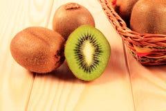 Kiwi in basket. On table Stock Photos