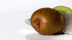 Kiwi being sliced in half on wet white background stock video