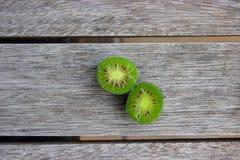 Kiwi berries (arctic kiwifruit) on wooden table Stock Images