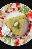 Kiwi bite size Cake. Small Kiwi Cake on floral decorated plate and dark background stock photo