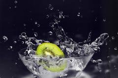 Kiwi caído en el vidrio de martini. Foto de archivo
