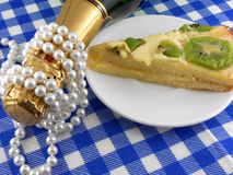 Kiwi cake close up at plate, champagne bottle and diamonds Royalty Free Stock Image