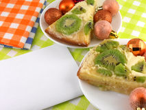Kiwi cake on plate with white paper and christmas balls set Royalty Free Stock Photo