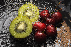 Kiwi and cherries in water Royalty Free Stock Photo