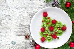 Kiwi christmas tree with raspberries, pomegranate and coconut with pine cones. funny food idea for kids