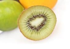 Kiwi close up with other blured fruit. A Kiwi close up with other blured fruit on white Stock Photos