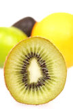 Kiwi close up with other blured fruit. A Kiwi close up with other blured fruit on white Royalty Free Stock Images